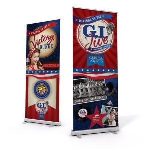 """two stand up banners. One with a 1950's styled woman with """"Victory Lounge"""" printed in a large bold font. The other has """"GI Jive"""" Printed on the top with retro imagery and patriotic design."""